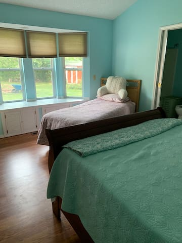 large bedroom walk in closet chest of drawers night stand with drawers lamps bay window. remote control TV on satellite