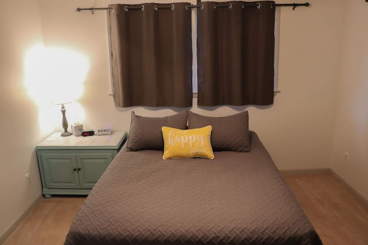Master bedroom with a queen-size bed.  There is a TV with Roku mounted on the wall, a multi-device charging station, alarm clock.  The closet has extra hangers, pillows, blankets, and other items that may be needed.