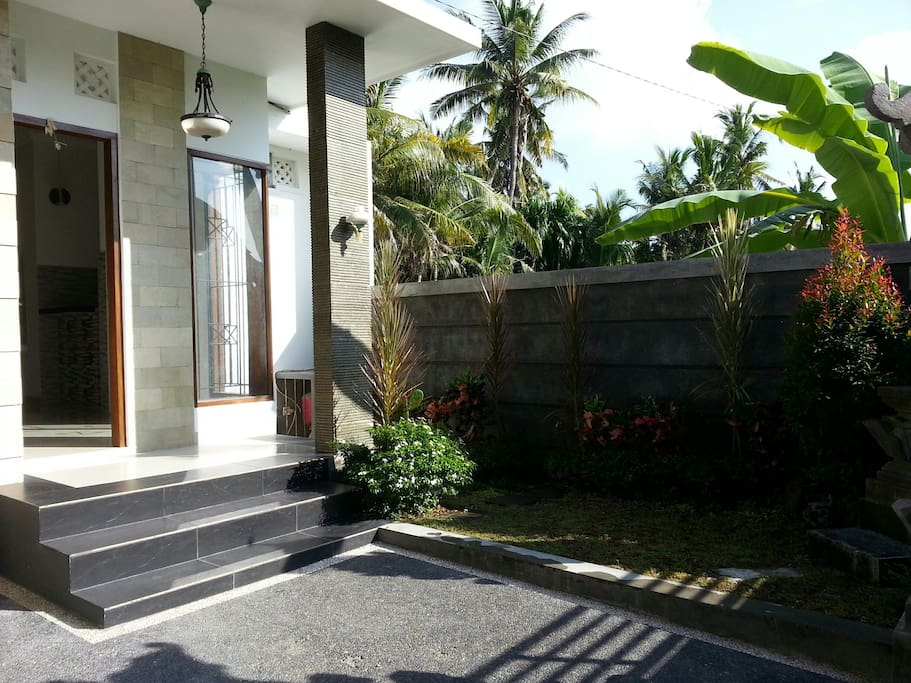 Clean, Modern touch of entrance with small garden and big carport for car and bikes.