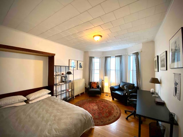 Bedroom has a queen size bed, two great chairs and a sizable desk next to a luggage area.
