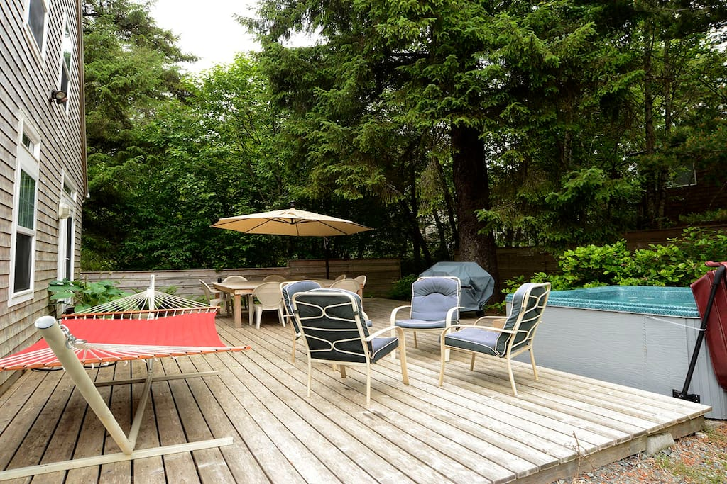 Large back deck with a semi-private hot tub, gas BBQ and a large wood patio table for 8