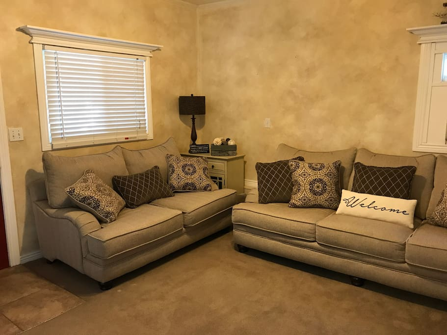"""A living room space with deep seating and 50"""" flat screen TV"""