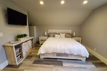 King Size bed with storage drawers and storage night stands with a jewelry drawer.  The lamps have built in wireless chargers or a USB charging port.  Echo Dot can tells time, weather or plays music.  The TV can rotate either direction for viewing.