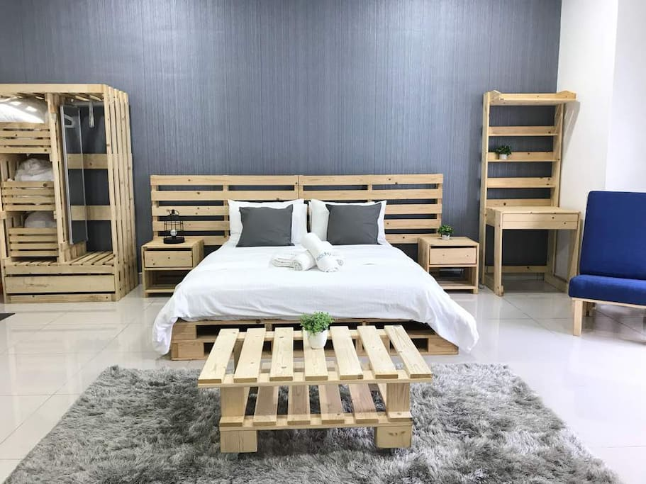 1 bright bedroom apartment with 1 queen size bed and a wooden open wardrobe.