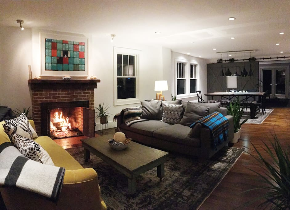 Spacious living room with comfy couches and a working fireplace.