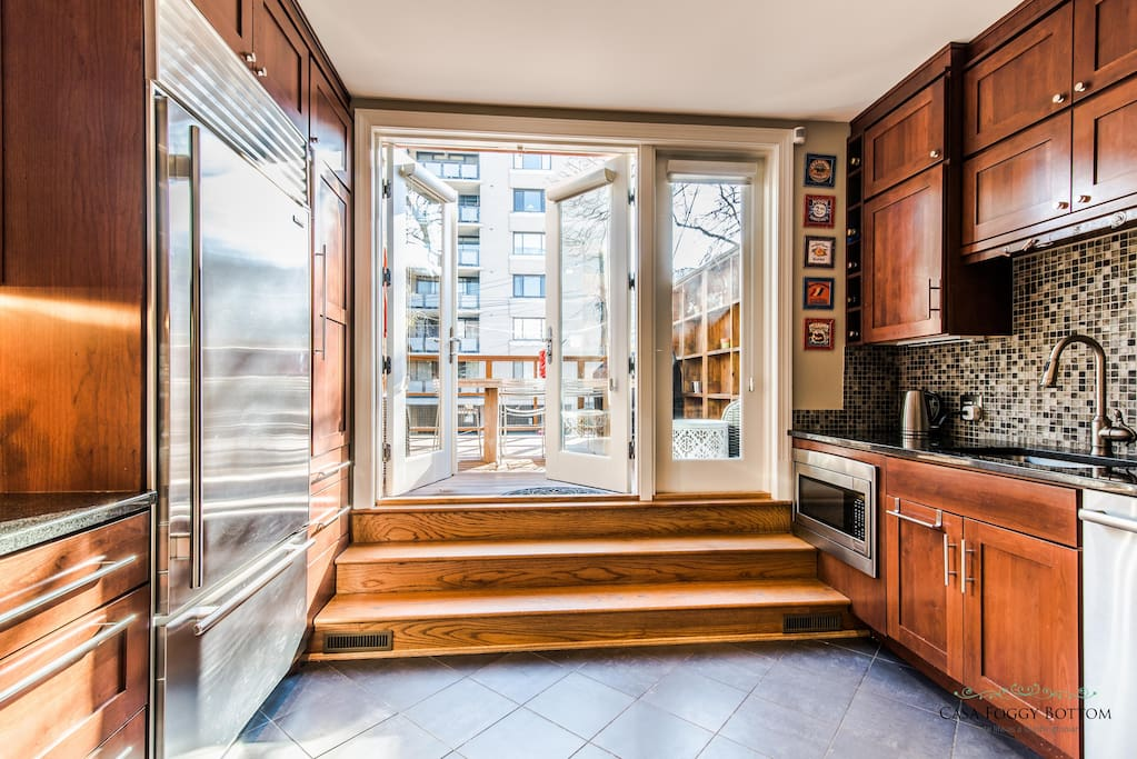 French doors leading to sun-filled deck with outdoor seating area for 6.