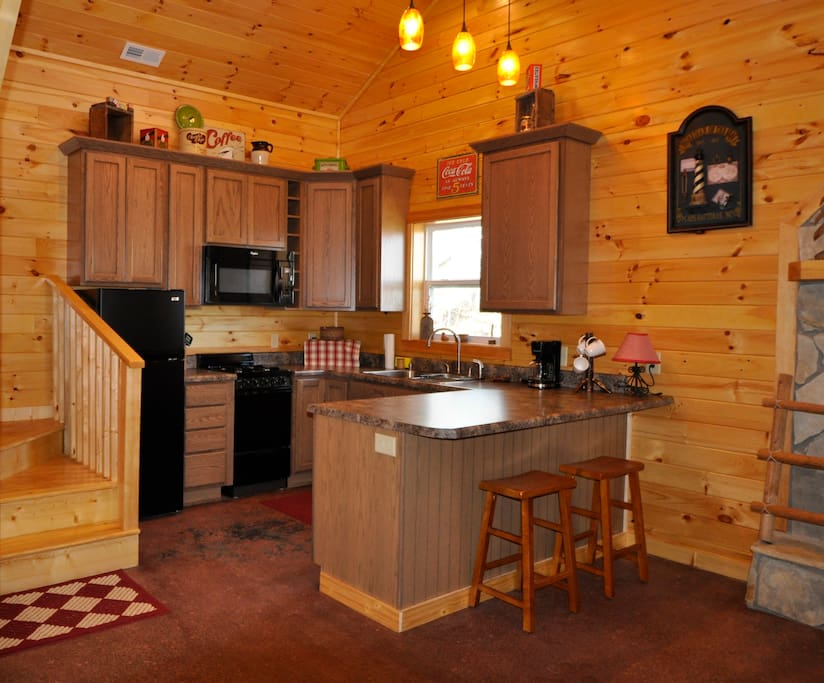 Fully stocked kitchen with gas stove, microwave, dishwasher, coffee maker & condiments.