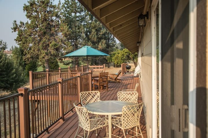 Large deck with BBQ, two dining tables and adirondacks
