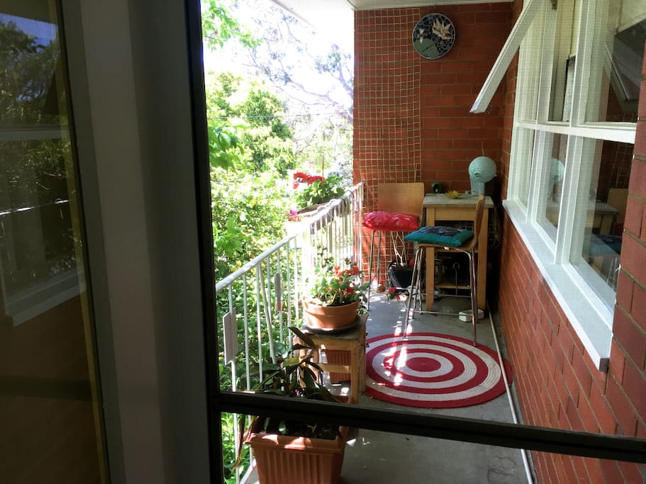 Balcony overlooks front yard with lemon tree and is shaded during heat of day.