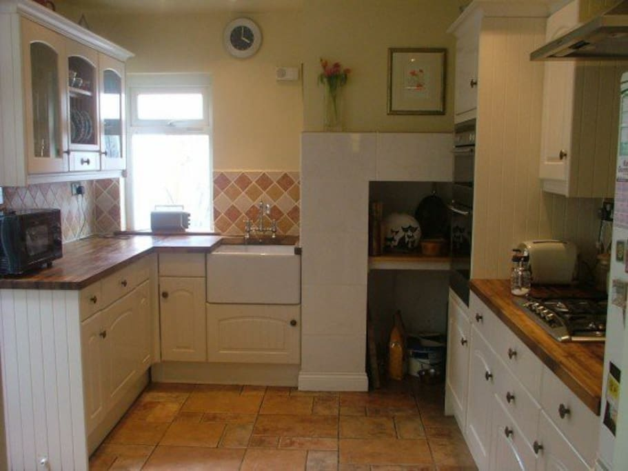 The kitchen is a small functional family kitchen with a small table for eating breakfast