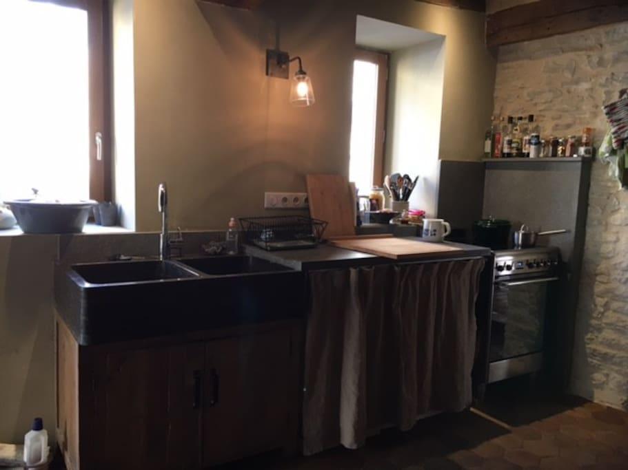 la cuisine tout confort, plan de travail en pierre des carrière de Montagny, évier en pierre, machine à laver la vaisselle, plan de cuisson induction.