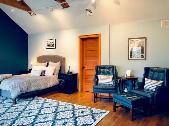 Upstairs guest room with seating area and door to a small room with a window perfect for a pack and play