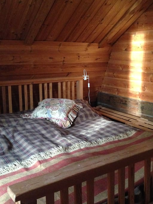 A bedroom with a large double bed and an extra bed on the side