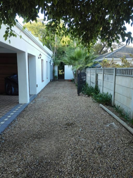 Driveway and parking towards flat. Secure, open parking for one vehicle and a trailer behind security gates next to the flat.