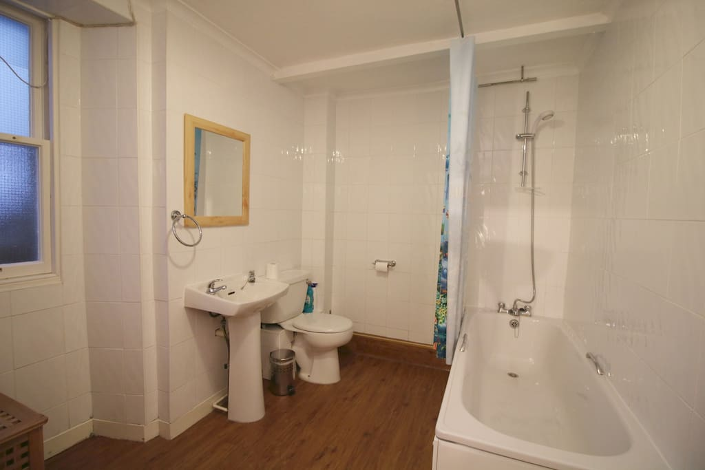 Large bathroom with shower over bath, window and extractor fan.