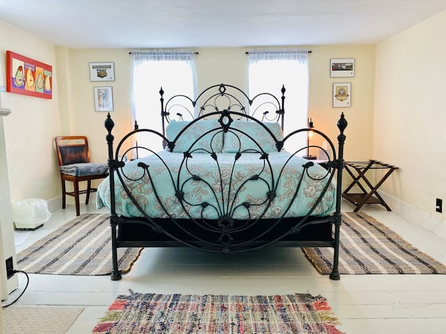 Welcome to bedroom #1.  Queen mattress with  soft and firm pillows.    Lamps on nightstands have built in USB charging ports.  Luggage rack on one side of the bed and extra blanket,  chair on other side.  Room also has a closet with dresser.