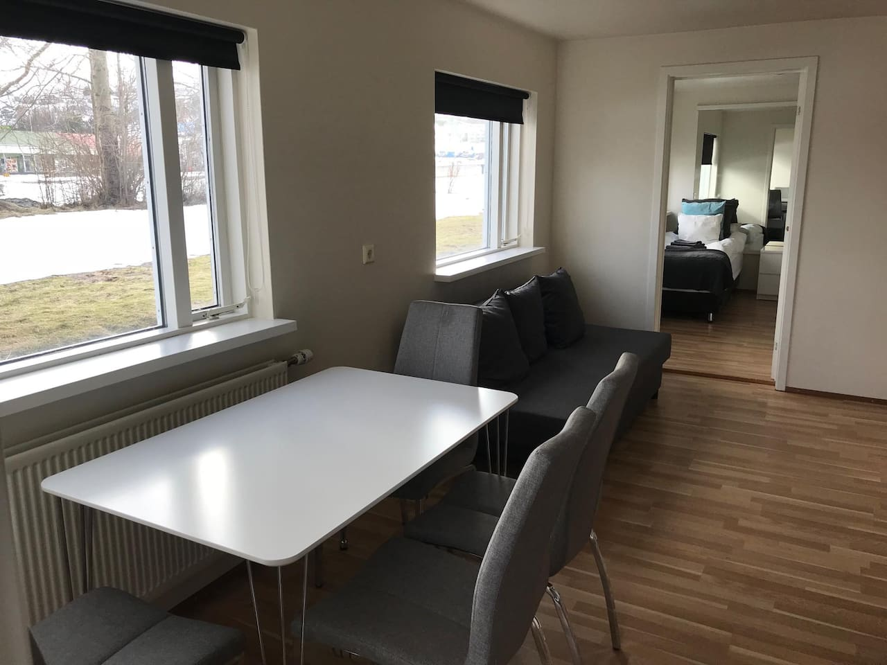 Sofa bed, dining table and a glimpse to one bedroom.