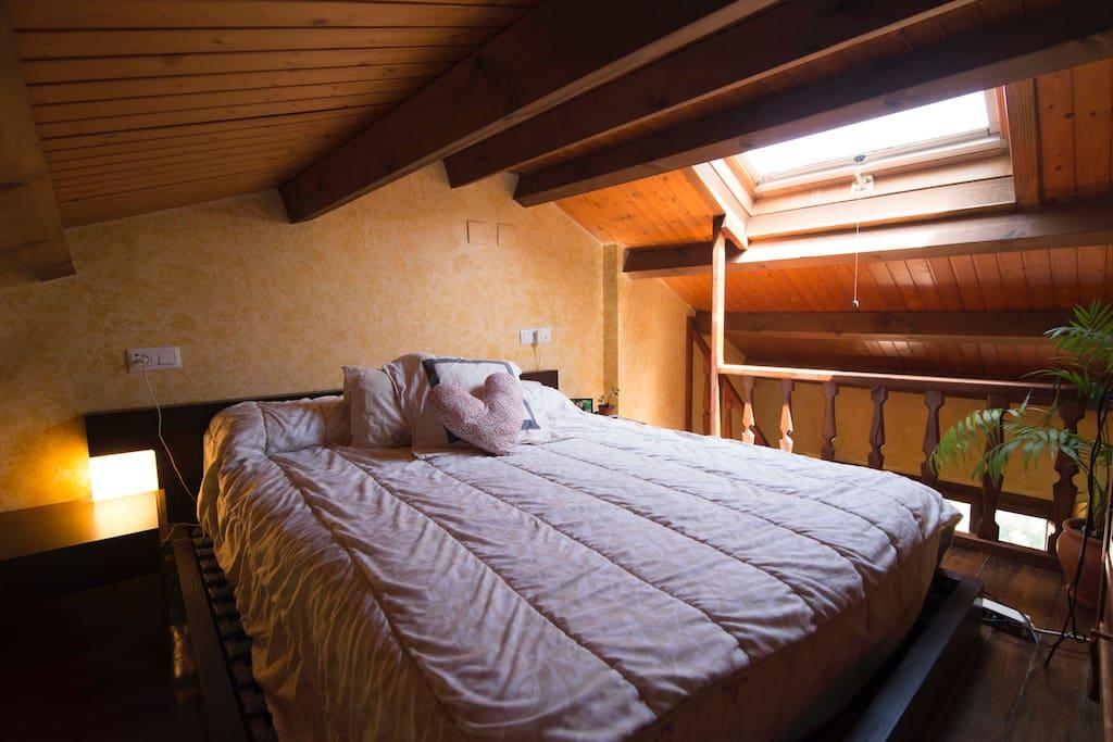 Altillo con techos de madera y ventana con vistas al cielo. Cama de matrimonio de 150x200