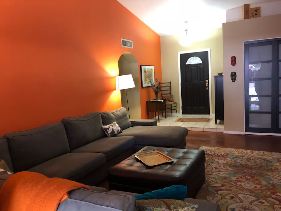 Welcoming entryway into livingroom with vaulted ceiling, large sectional, TV and stereo.