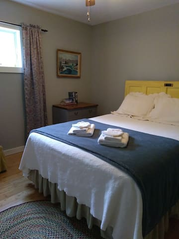 This bedroom has a comfy queen size bed and small dresser.
