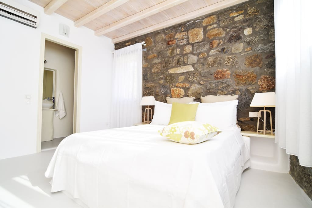 Master Bedroom 1 with wooden ceiling , stone walls and with en-suite batrhroom