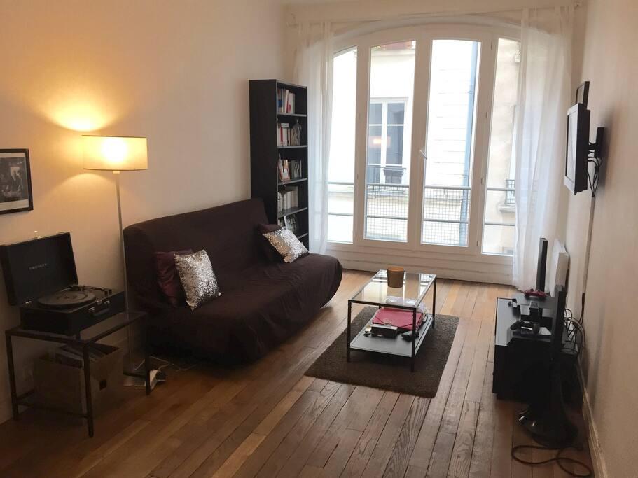 Dès l'entrée, un grand salon accueillant et lumineux avec télévision fixée au mur et canapé lit deux places très confortable