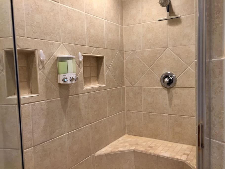 Spacious tiled walk-in shower with dispensed eco friendly bath products
