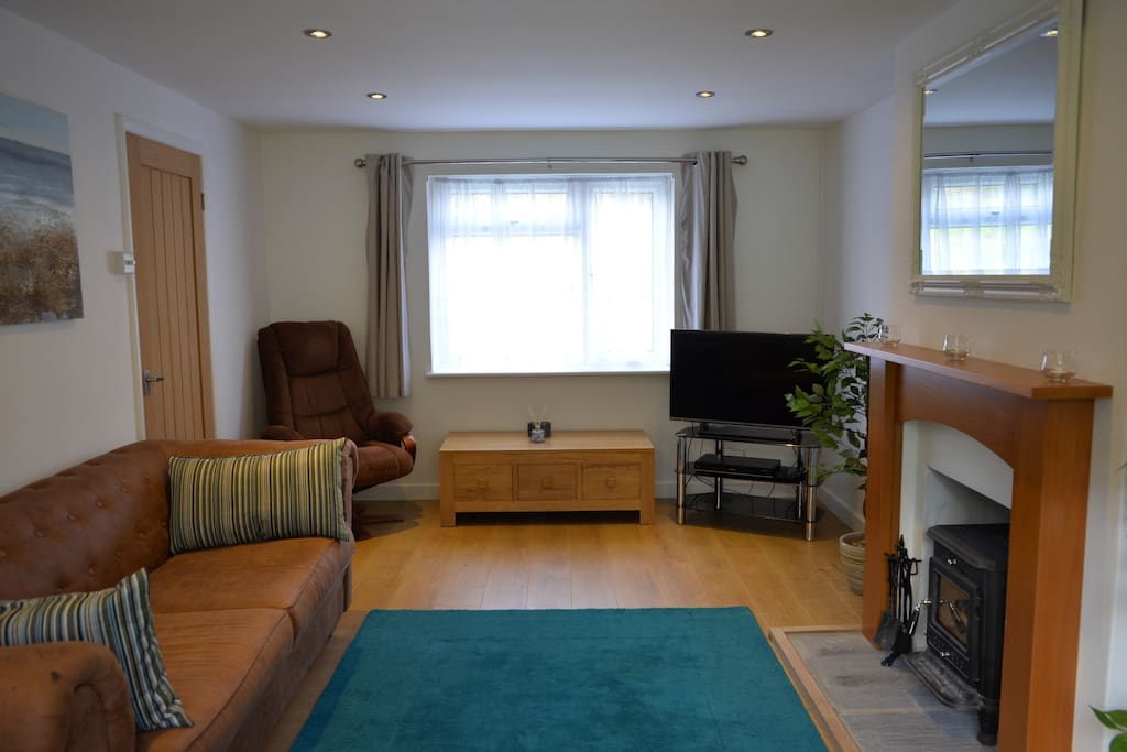 Spacious Living room with wood burning stove, smart TV, and blu-ray / DVD player & HDD recorder.