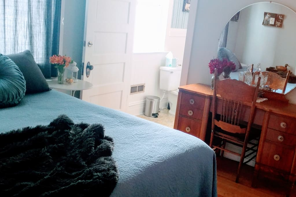 Room 3 bed, vanity, leading into the bathroom.