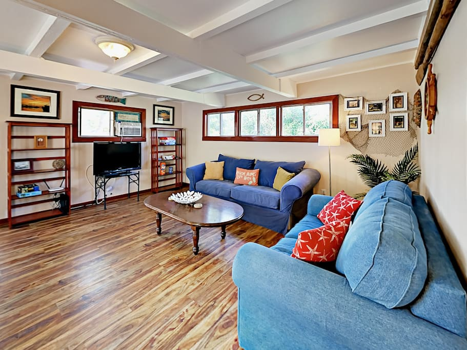 """A large sofa and love seat surround the 38"""" flat screen TV with cable in the living room."""