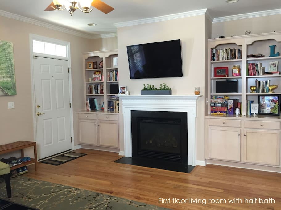 Living room: large wall-mounted TV, fireplace