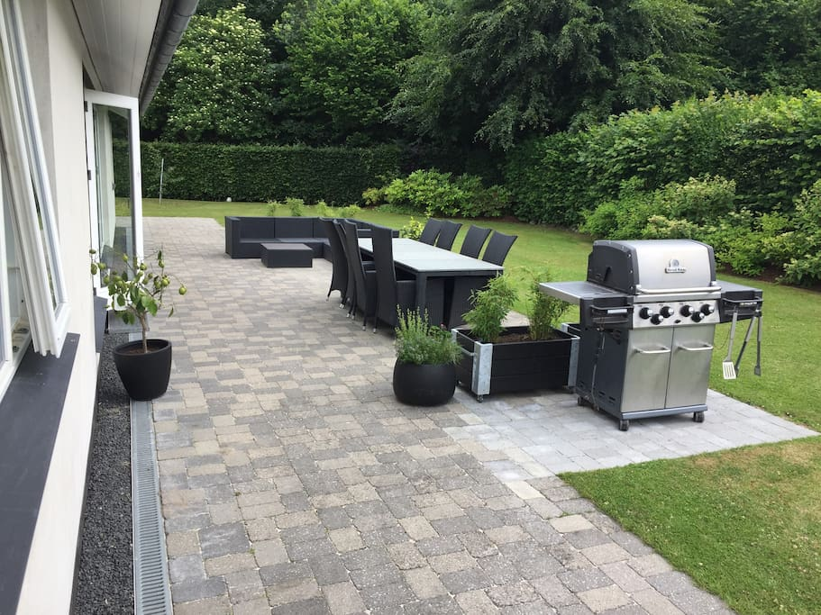 Terrace with lounge sofa, dinning table and gas barbecue