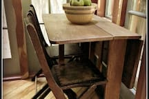 The antique oak breakfast table comes with four chairs and folds out.