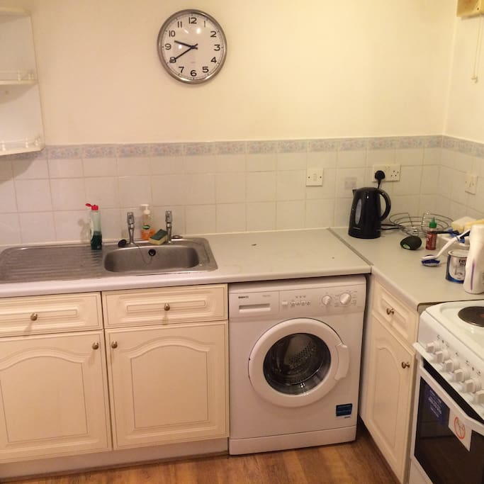 Kitchen with fridge, freezer, cooker and washer.