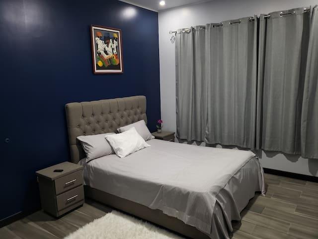 La habitación grande con cama Queen, cuenta con balcón para fumar.