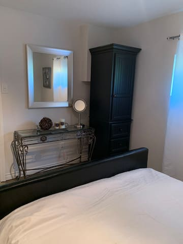 Bedroom with Queen bed & storage with extra pillows, sheets, blowdryer etc. Vanity mirror with 10x magnification lights up.