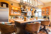 Solid Wood plank island for appetizers, dinner and socializing. Candles everywhere. Robust custom barstools for lounging