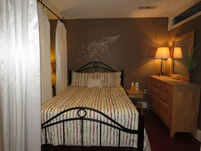 Queen sized comfort bed with curtains that can be drawn to completely surround the bed for privacy.