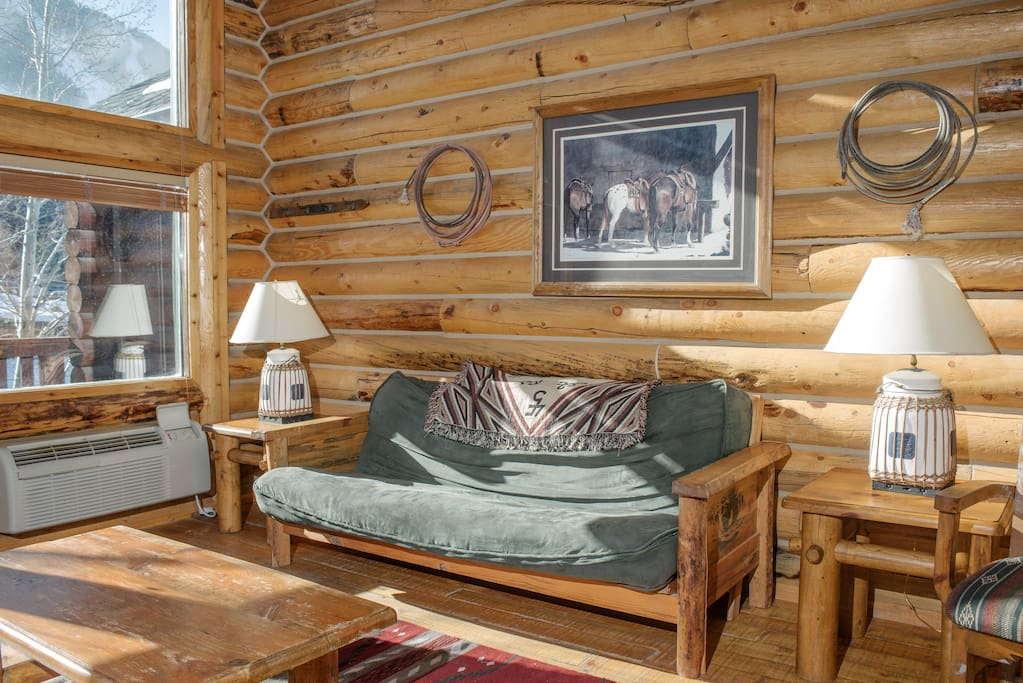 Enter into a western-themed living room, where 6 can warm up by the fire