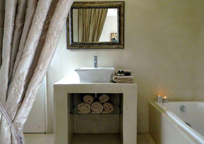 En-suite bathroom with bath and shower