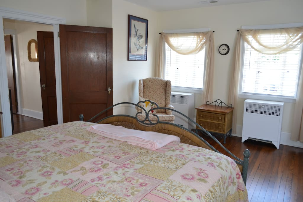 King bed with sitting area, dressers and closet.