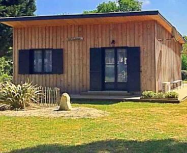 Maison avec jardin et belle terrasse en bois.