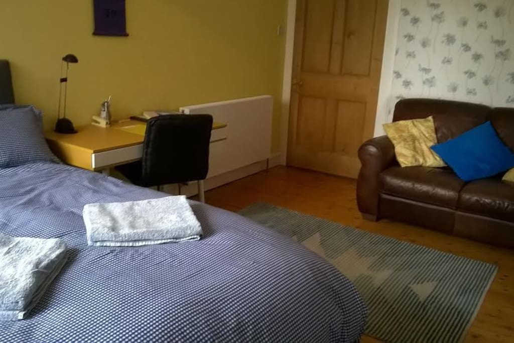 Spacious bedroom with comfy sofa, desk, and full length mirror