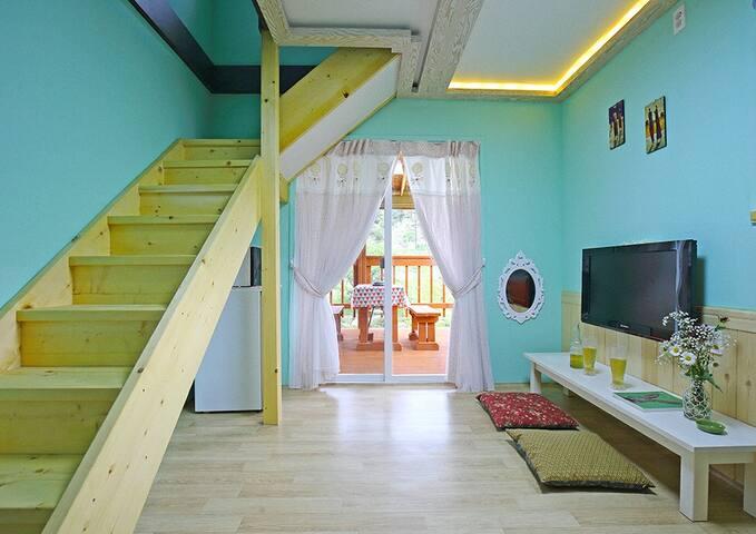 민트색컬러와 화이트의 커튼으로 아기자기한 느낌을 주는 복층형 민트객실
