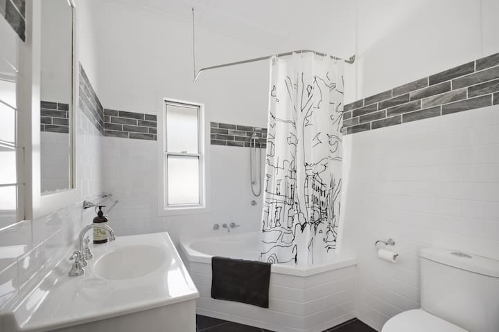 Main bathroom with shower over large bath