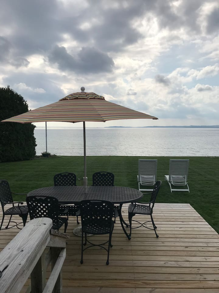 This is what you see when you walk out the lake-side doors - beautiful and private lakefront setting and sandy beach. A deck for outdoor eating. 4 lounge chairs for outdoor sunning!