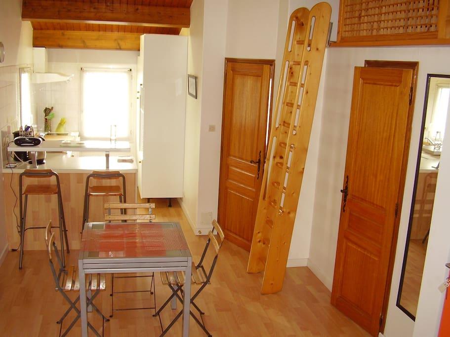 La pièce à vivre avec le coin cuisine, le coin salle à manger et l'escalier montant à la mezzanine avec ses 2 lits de 90 (lit pour une personne)