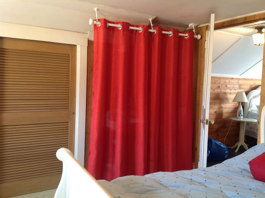 Shows closet and curtains drawn on en suite toilet and sink.
