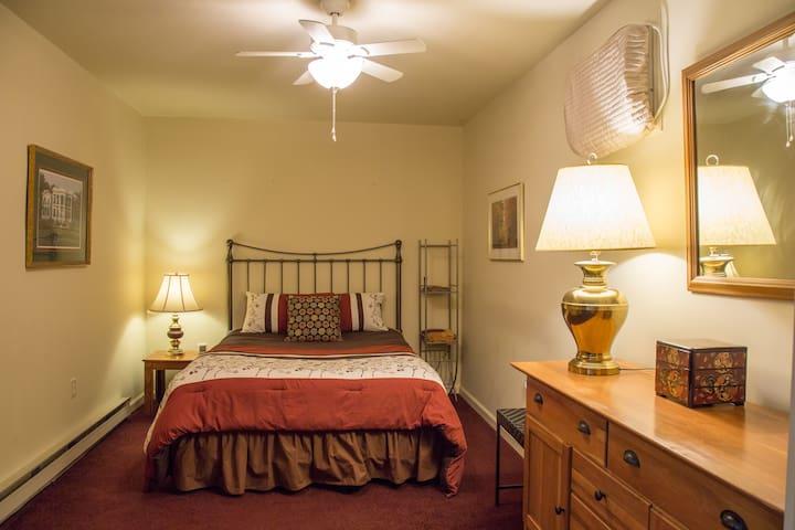 Queen bed in large bedroom