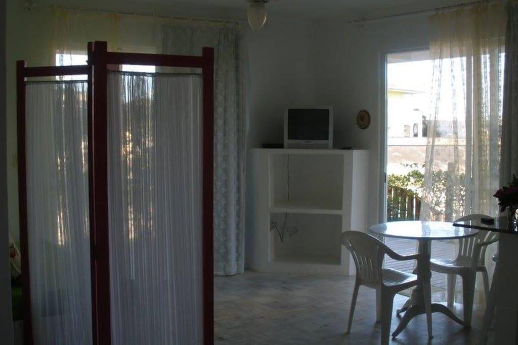 Vista da cama para sala. Duas portas amplas com varanda.